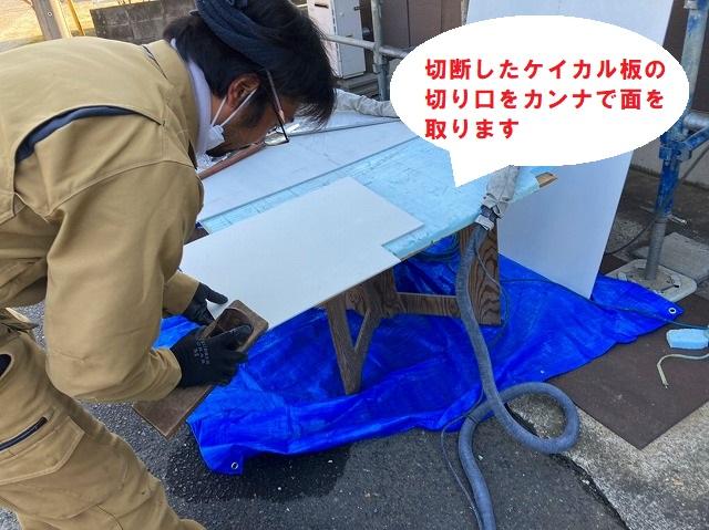 切断したケイカル板の切り口を鉋で面取りする職人