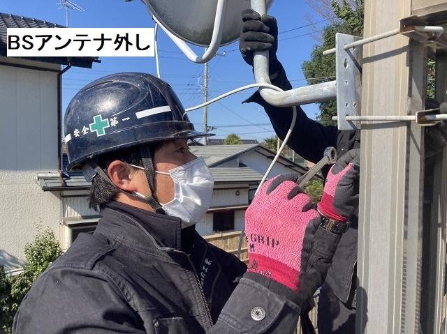 ベランダ手すりに設置されたBSアンテナを撤去する作業員
