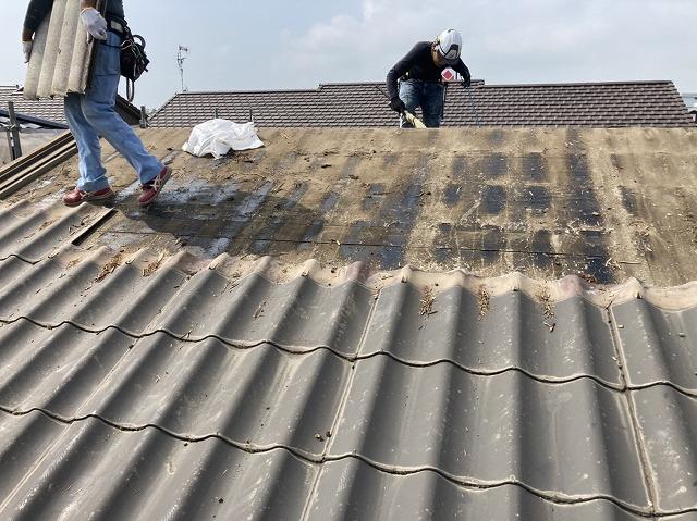 撤去した屋根材を運ぶ職人と、清掃する職人