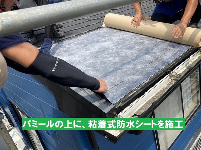 パミールの上に粘着式防水シートを施工する職人
