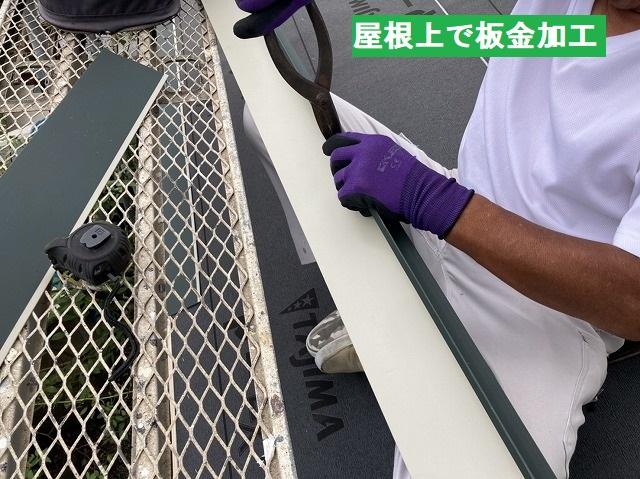 屋根の上で屋根の役物板金を加工する職人