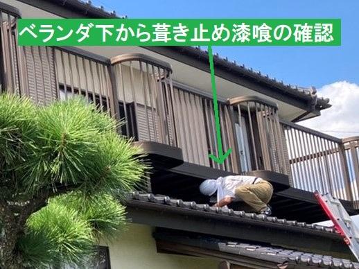 下屋根からベランダ下を覗き込むスタッフ