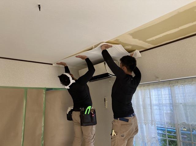 二名の職人が協力して天井クロスを貼る