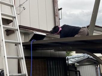 下屋根に登り開口部から霧よけの軒天を覗き込む職人