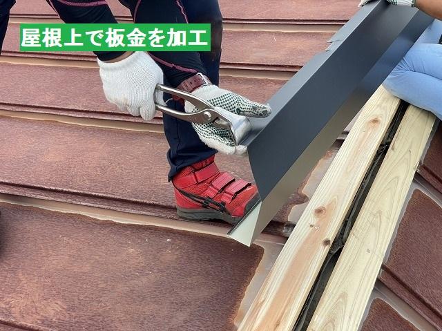 屋根上で棟板金を加工する職人