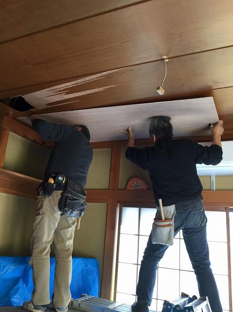 目透かし天井にべニアを上張りする2名の職人