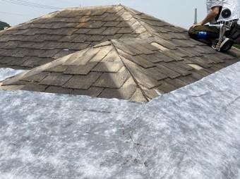 粘着式防水シートを既存屋根材に施工する職人