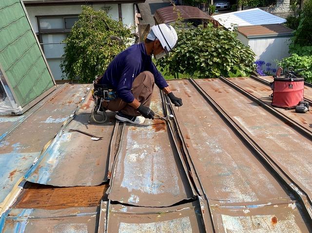 丸ノコで瓦棒屋根を解体する職人