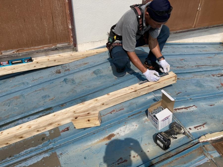 屋根上で木下地を切断する職人