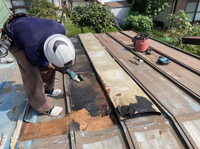 既存の縦葺きトタン屋根を解体する職人