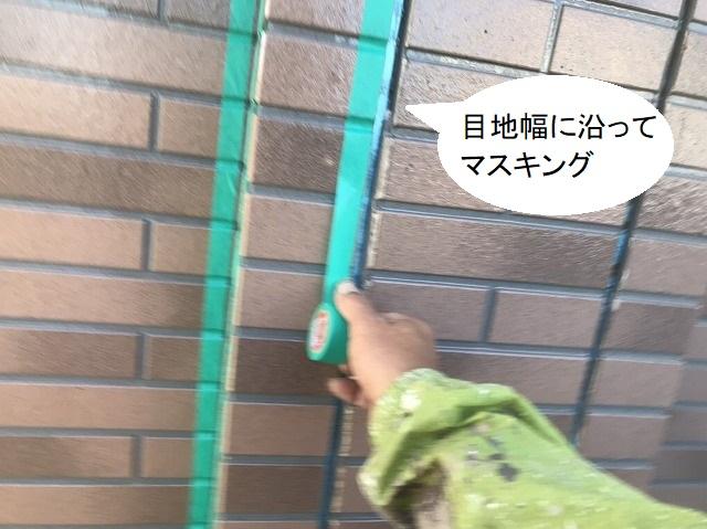 サイディングの目地に沿ってマスキングテープを貼る職人