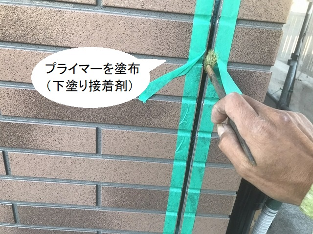 サイディングの目地に接着プライマーを塗布する職人