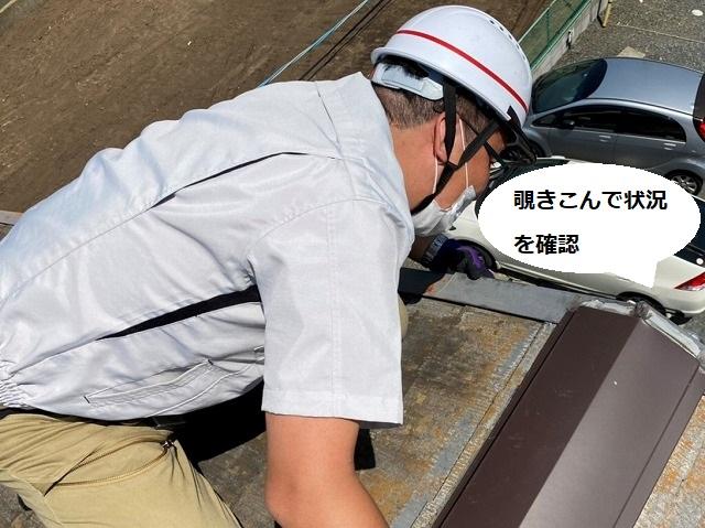 ケラバ板金を屋根の上から覗き込むスタッフ