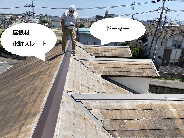 ドーマーが設置された化粧スレート屋根を歩くスタッフ