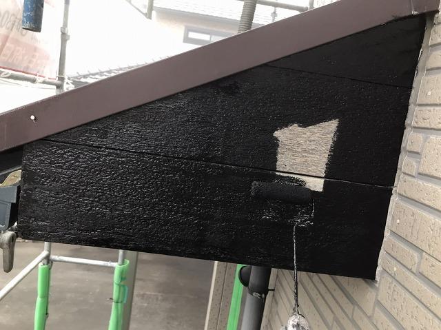 ローラーで木製破風板に黒い塗料を塗布