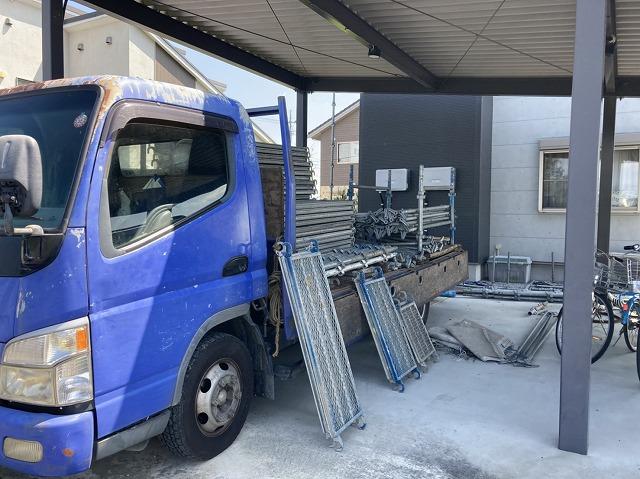 青いトラックに積まれた足場材
