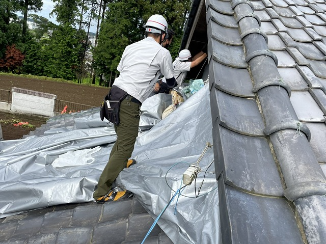 屋根にシルバーシートを掛けるスタッフ