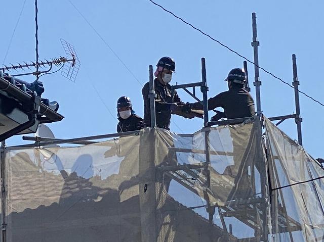 2階の屋根部で解体した瓦をバケツリレーする縮人