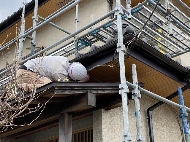 玄関軒先屋根から施工部位を覗き込みながら最終チェックする店長