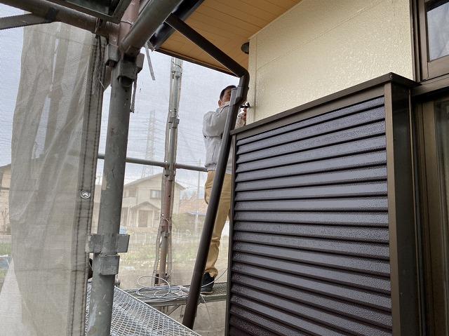 竪樋を外しハイヤーブラシを配管に通す職人
