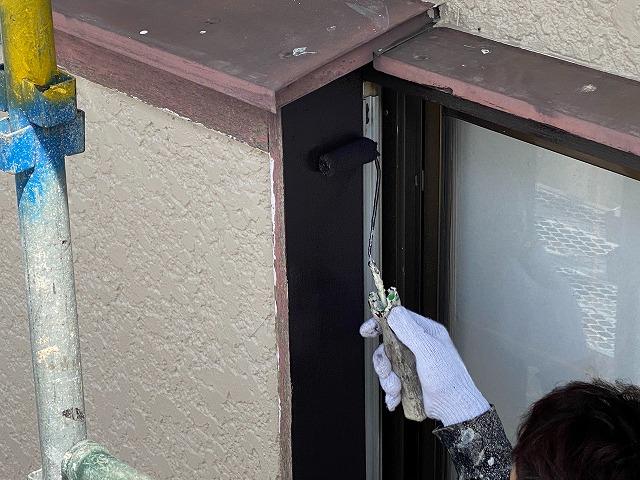 ローラーを使い茶色の塗料を戸袋に塗布する職人