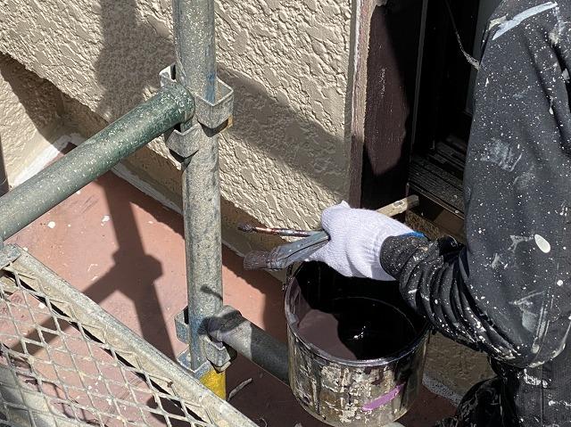 刷毛とローラーを使い分けながら戸袋を塗装する職人