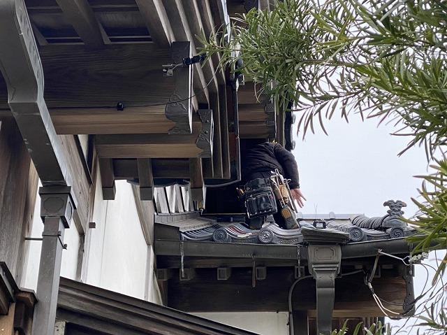妻側の屋根に慎重に乗る職人
