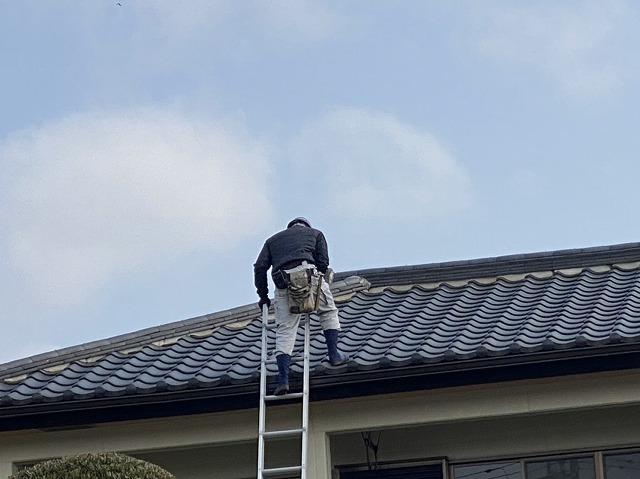 梯子で2階の屋根に登る職人