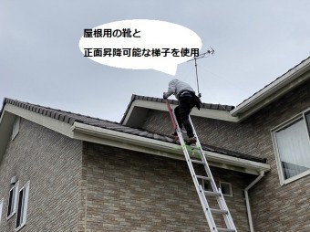 屋根用の靴を履き正面から昇降できる梯子で屋根に登った職人