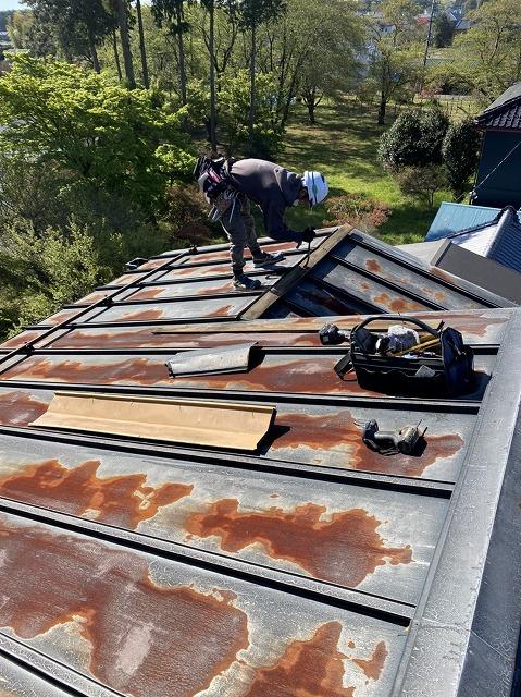 錆付いた板金屋根の棟を解体する職人