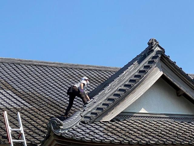 入母屋玄関屋根の急勾配で登るのに苦労しているスタッフ