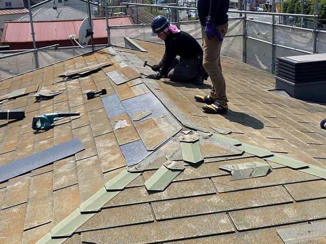 スレート屋根を部分的に差し替え修理を行う職人
