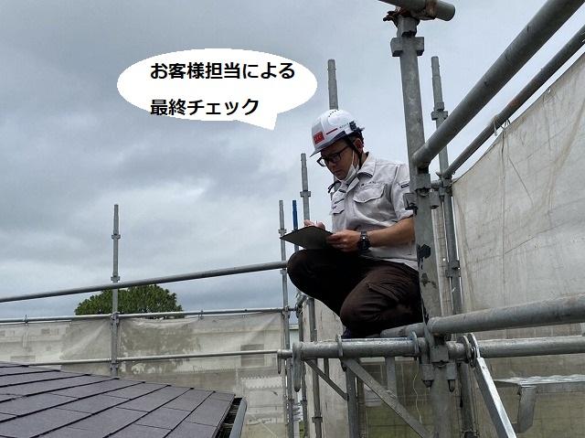 屋根塗装が完了し最終チェツクを行うヘルメットを被ったスタッフ