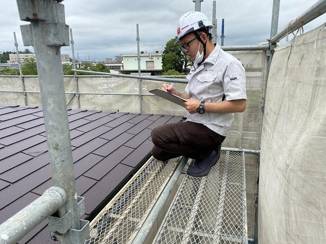屋根修理状態をチェツクするスタッフ