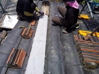 型枠に強力なんばん漆喰を詰め入れる二人の職人