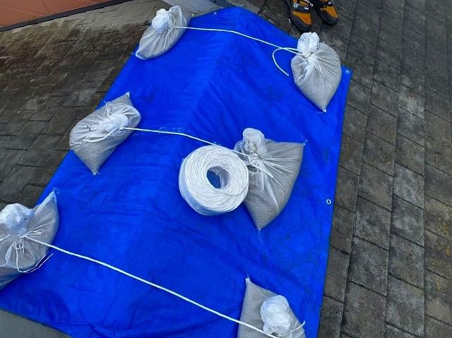 雨漏り部をブルーシートで養生し土嚢をロープでくくる