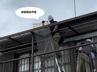 風に煽られながら2階のテラス波板を撤去する職人