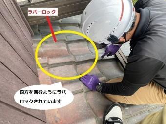四方を囲んでいた瓦のラバ―ロックをカッターで切るスタッフ