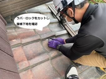 屋根下地を確認する為に瓦のラバ―ロックを撤去するスタッフ