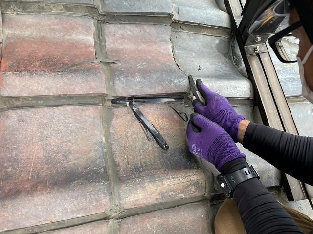 瓦に施された分厚いラバ―ロックをカッターで切る