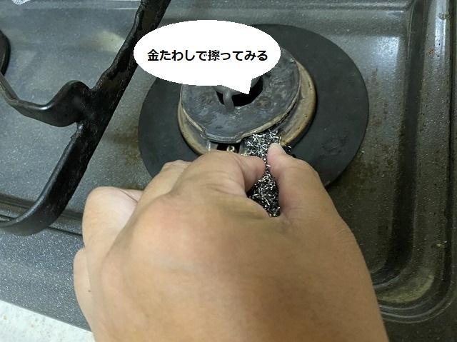立ち消え安産装置部を金たわしで擦っているスタッフの手
