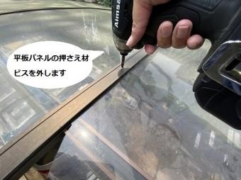 平板パネルの押さえ材をインパクトドライバーで外している職人の手元