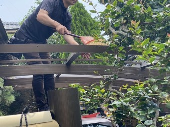 脚立に乗り、カーポートアルミ枠の清掃を行う職人