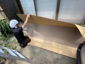 カッターで包装を開口している職人
