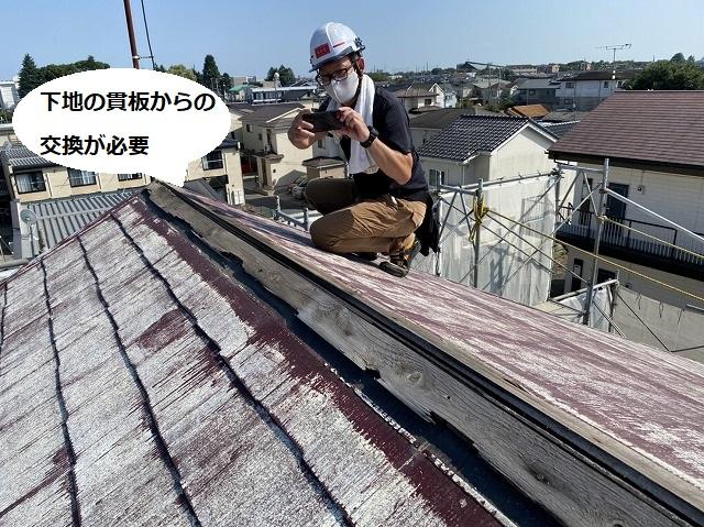 ケラバ側から破損棟部を撮影するスタッフ