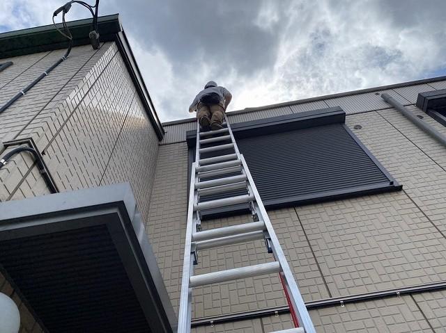 梯子を上るスタッフを地上から見上げながら撮影