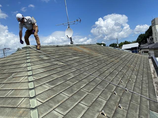 屋根の実寸を測るため屋根の棟からスケールを伸ばし計測するスタッフ