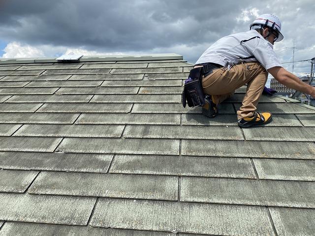 屋根の傾斜に耐えながら屋根の状態を確認するスタッフ