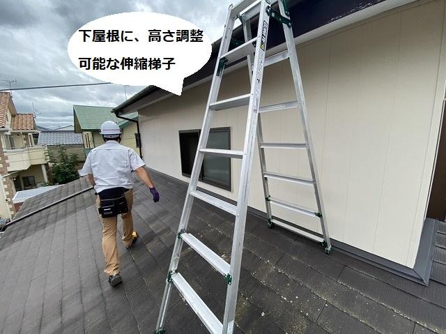 下屋根に高さ調整可能な伸縮脚立を準備するスタッフ