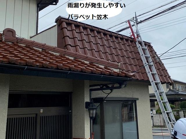 パラペット屋根に二連梯子を掛けるスタッフ